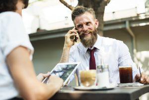 Mann prater i telefon på en kaffé